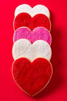 Galletas en forma de corazón para el día de san valentín sobre fondo rojo.