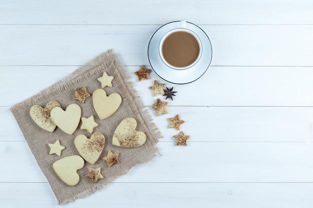 Galletas en forma de corazón y estrella en un pedazo de saco con galletas estrella, taza de café plana yacía sobre un fondo de tablero de madera blanca