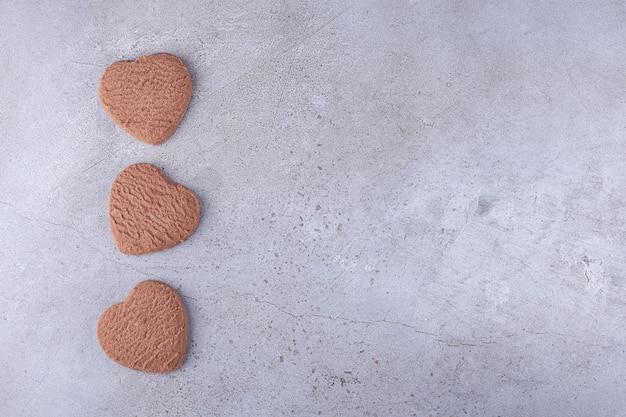 Galletas en forma de corazón frescas fragantes colocadas en piedra.