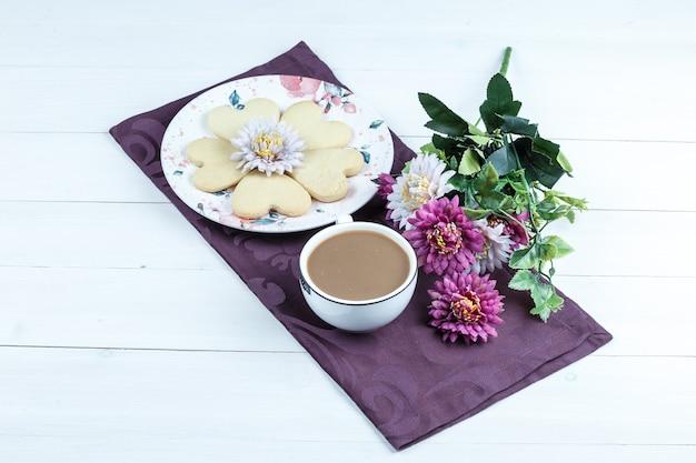 Galletas en forma de corazón, taza de café en un mantel púrpura con flores vista de ángulo alto sobre un fondo de tablero de madera blanca