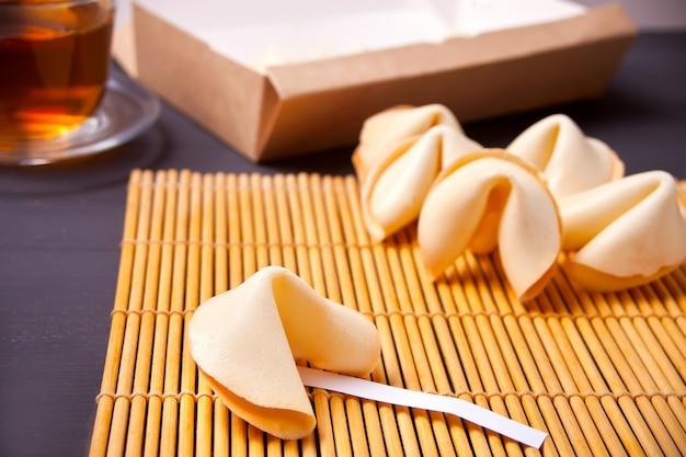 Galletas de la fortuna y taza de té en la mesa de madera
