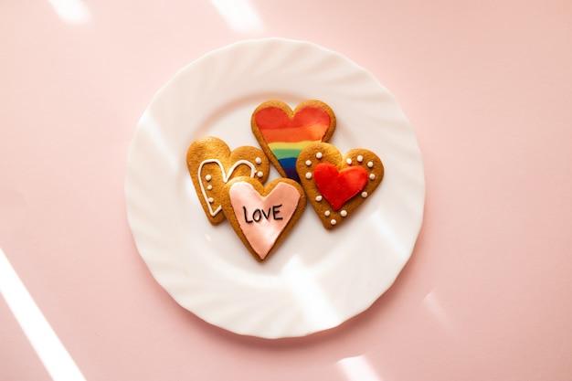 Galletas glaseadas en forma de corazón. lgbt y texto de amor. hornear con amor para el día de san valentín, el amor y el concepto de diversidad.