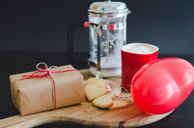 Galletas y globo en forma de corazón, taza de café y caja envuelta