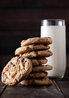 Galletas sin gluten de caramelo dulce avena sobre fondo de madera vieja con vaso de leche