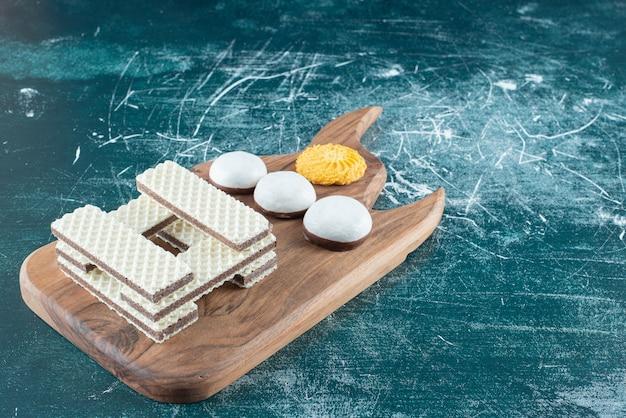 Galletas y gofres crujientes de vainilla sobre tabla de madera.
