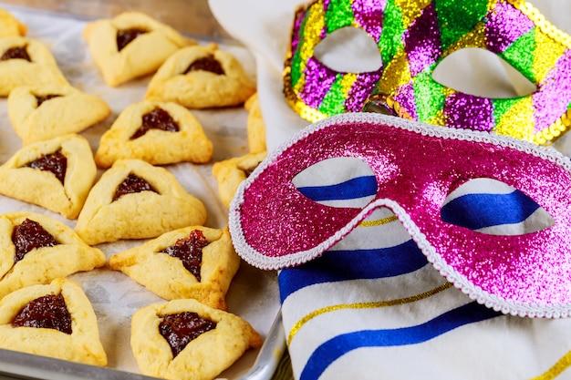 Galletas hamantaschen en bandeja para hornear con tallit y máscara