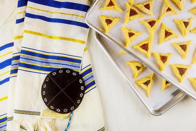 Galletas hamantaschen crudas en bandeja para hornear con kippa y tallit