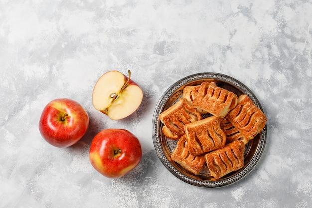 Galletas de hojaldre rellenas de mermelada de manzana y manzanas rojas frescas sobre hormigón ligero