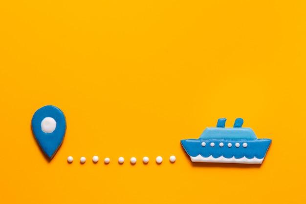 Galletas de jengibre barco y punto del mapa sobre fondo amarillo