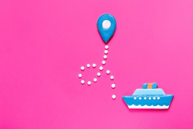 Galletas de jengibre barco y punto del mapa sobre fondo rosa
