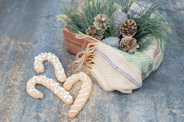 Galletas de jengibre y canasta de decoraciones navideñas en superficie de mármol. foto de alta calidad