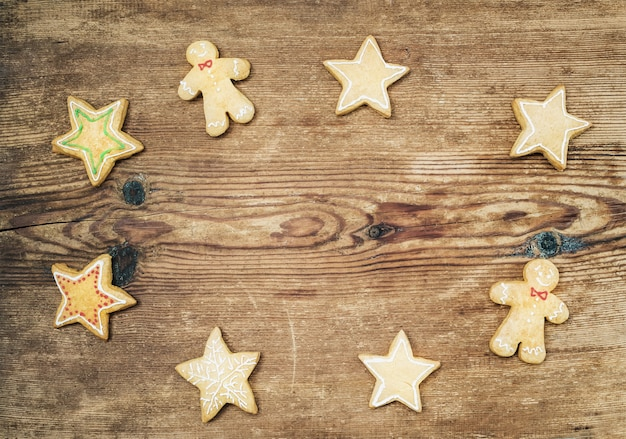 Galletas de jengibre caseras de navidad de hombre y estrellas sobre madera rústica, vista superior