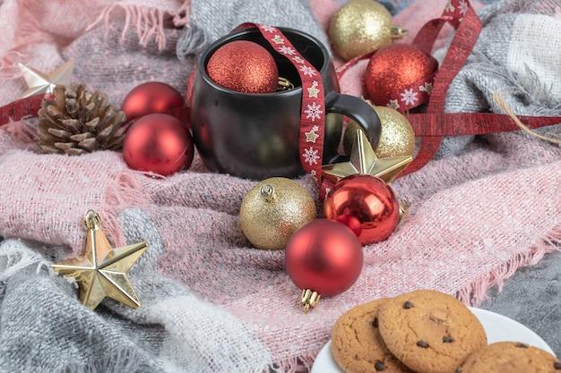 Galletas de jengibre crujientes en un platillo blanco con una taza de bebida y adornos navideños alrededor