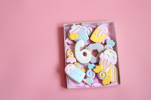 Galletas de jengibre festivas coloridas de diferentes formas cubiertas con esmalte sobre fondo rosa.