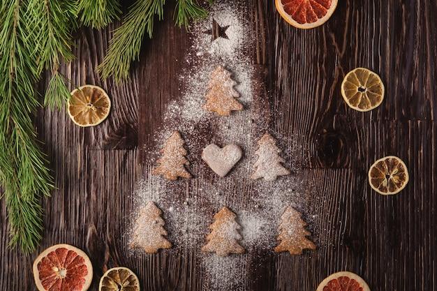 Galletas de jengibre en forma de abeto de navidad y con azúcar en polvo sobre mesa de madera, frutas secas de cítricos, rama de abeto, vista superior