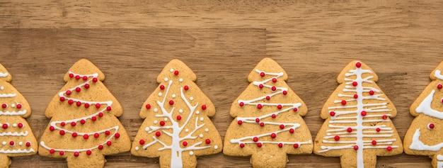 Galletas de jengibre de forma de árbol de navidad en una fila en el fondo de madera bandera