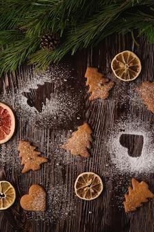 Galletas de jengibre en forma de corazón y abeto de navidad, azúcar en polvo sobre mesa de madera, frutas secas de cítricos, rama de abeto, vista superior