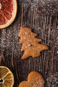 Galletas de jengibre en forma de corazón y abeto de navidad, azúcar en polvo sobre mesa de madera, frutas secas de cítricos, vista superior