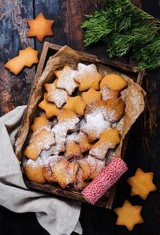 Galletas de jengibre en forma de estrella de navidad año nuevo caseras en caja de madera sobre superficie de madera vieja