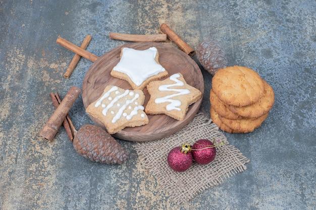 Galletas de jengibre en forma de estrella en un plato con bolas de navidad. foto de alta calidad