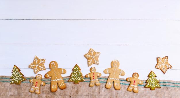 Galletas de jengibre en forma de hombres, estrellas y árboles sobre tela de saco y superficie de madera blanca. concepto de navidad