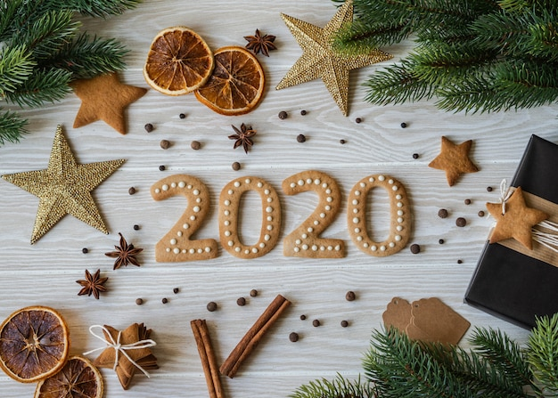 Galletas de jengibre en forma de números y 2020 galletas de jengibre de año nuevo de madera blanca. vista superior. envases de temporada, especias y atributos de año nuevo.