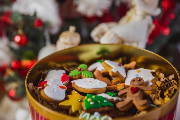 Galletas de jengibre en una gran caja roja en el árbol de navidad. de cerca.