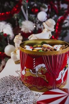 Galletas de jengibre en una gran caja roja en el árbol de navidad.