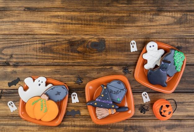 Galletas de jengibre de halloween, calabaza, lápida, sombrero de bruja, gato negro en placas sobre mesa de madera con espacio de copia.