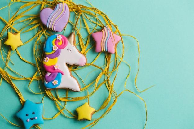 Galletas de jengibre hermosas, brillantes y con figuras para las vacaciones sobre un fondo turquesa