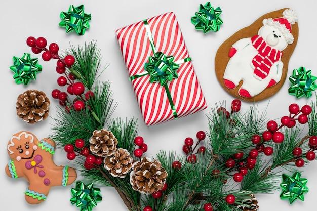 Galletas de jengibre de navidad y adornos de año nuevo en superficie blanca. tarjeta de felicitación con regalo, ramas de abeto, piñas y bayas de acebo rojo.