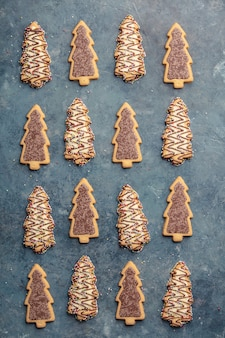 Galletas de jengibre de navidad en forma de árbol de navidad sobre fondo azul.