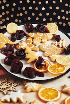 Galletas de jengibre de navidad y naranja seca y especias en mesa blanca. pastel, mermelada en rollos en un plato