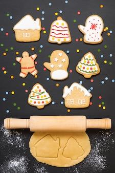 Galletas de jengibre de navidad, rodillo y masa sobre fondo negro