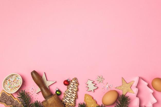 Galletas de jengibre navideñas en forma de árbol de navidad e ingredientes para hornear
