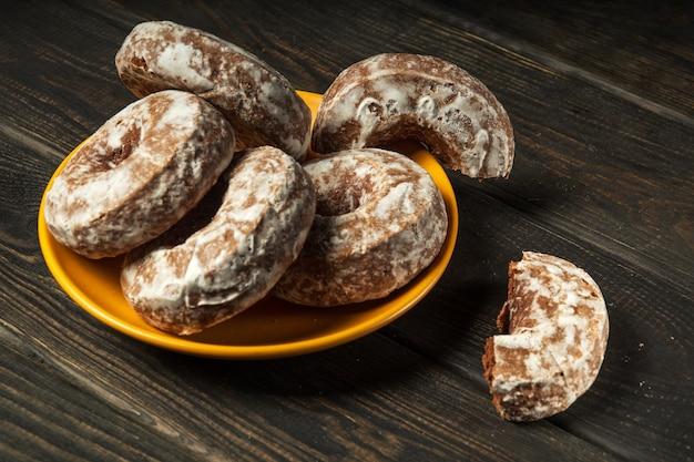 Galletas de jengibre redondas caseras con glaseado en una placa amarilla. idea para un delicioso desayuno o cena. vista superior
