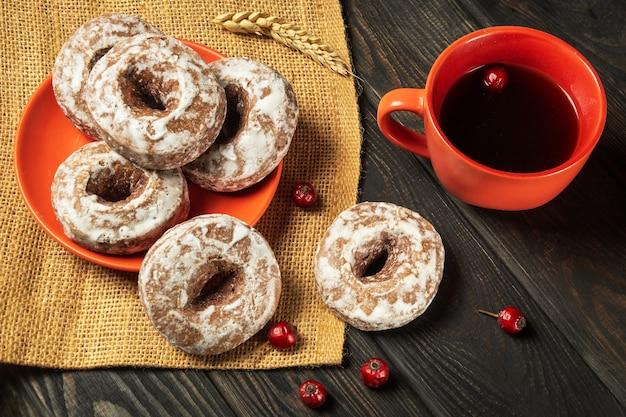 Galletas de jengibre redondas caseras con glaseado en un plato y té caliente de rosa mosqueta. idea para un delicioso desayuno o cena.