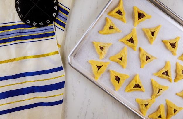 Galletas judías crudas en la bandeja del horno con kippa y tallit.
