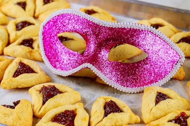 Galletas judías con mermelada en la bandeja del horno con máscara.