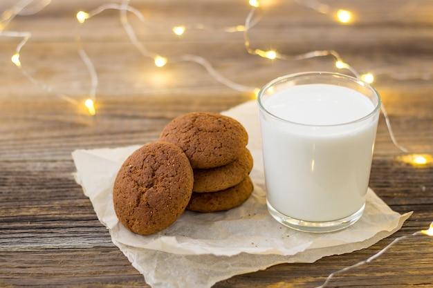Galletas y leche en vaso para santa claus delante de un bokeh de luz navideña.