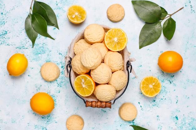 Galletas de limón caseras con limones en superficie clara