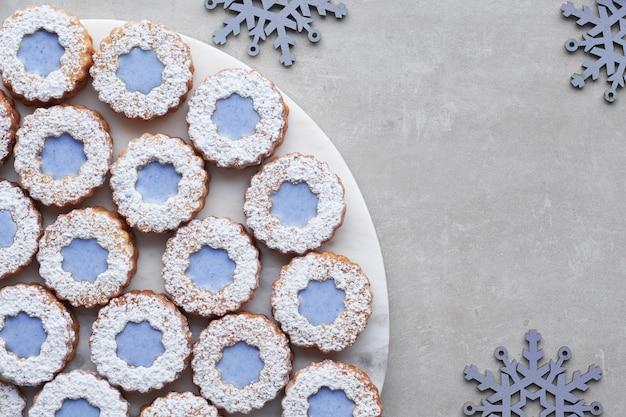 Galletas linzer de flores blancas y azules sobre piedra clara decoradas con copos de nieve azules