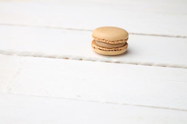 Galletas de macarrón marrón dulces y deliciosas en la superficie de madera