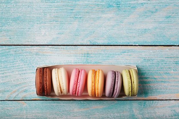 Galletas de macarrones de diferentes colores en una caja sobre un fondo de madera azul, viejo de color azul.