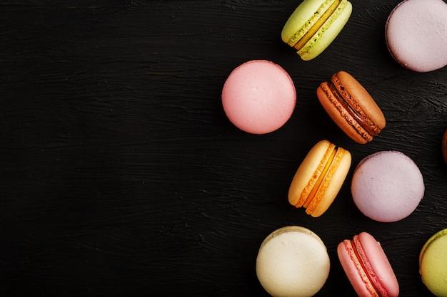 Las galletas de macarrones de diferentes colores se encuentran sobre un fondo negro con textura. espacio libre. bodegón de confitería.