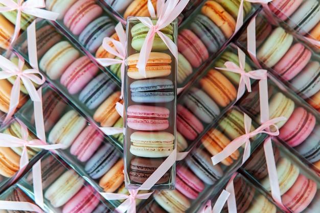Galletas de macarrones de diferentes colores en un paquete con un lazo, muchas cajas con galletas en forma de textura.