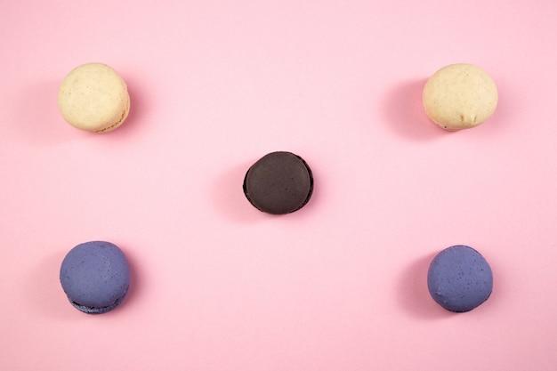 Galletas de macarrones multicolores sobre fondo rosa aislado