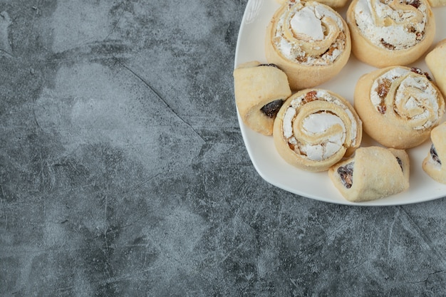 Galletas de mantequilla con azúcar en polvo en un plato de cerámica blanca.