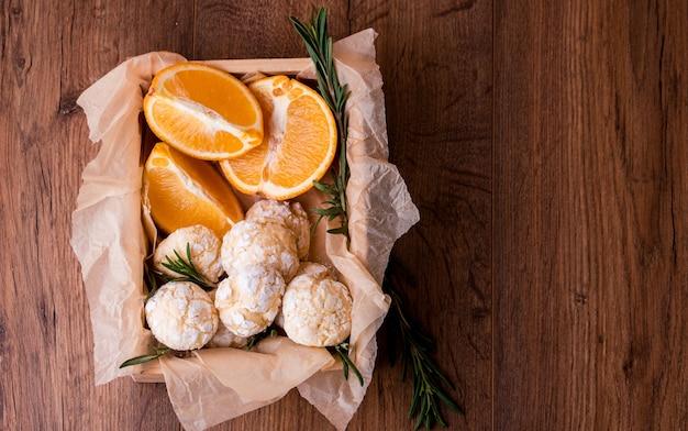 Galletas de mantequilla de naranja con ramitas de semarin, con naranja fresca y jugo sobre la mesa.