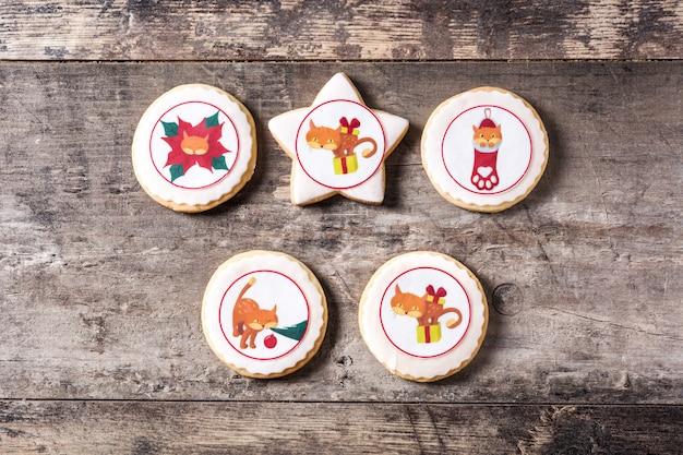Galletas de mantequilla de navidad decoradas con gráficos navideños en mesa de madera